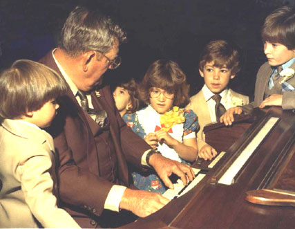 Marvin playing for his great grandchildren, 1982